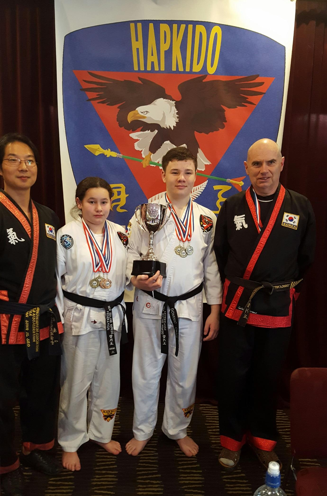 Winner of the 1st Oceania Cup Dominic Chan with his sister Yasmin Chan flanked by GM Scott and Callum Forbes